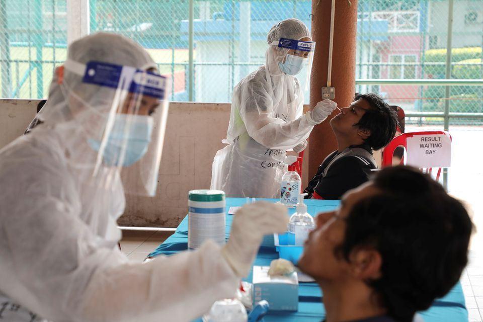 Medical workers collect swab samples from people at a coronavirus disease (COVID-19) testing centre in Petaling Jaya, Malaysia January 25, 2021. REUTERS/Lim Huey Teng