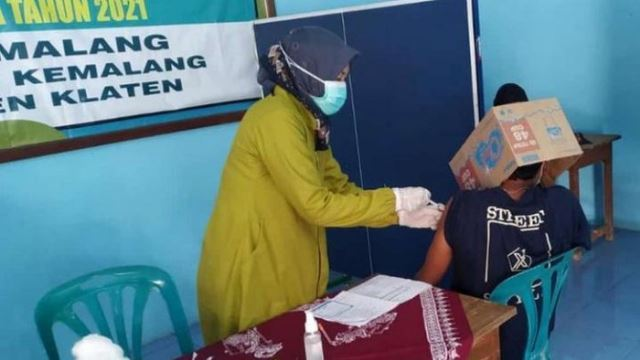 scared of getting vaccinated, young man in indonesia covers his whole face with cardboard box